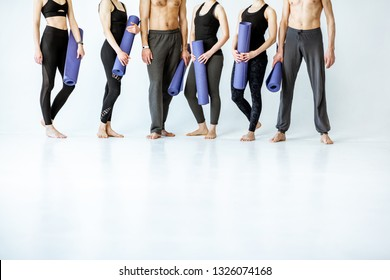 Group of young athletic people in sportswear standing with fitness mats on the white background