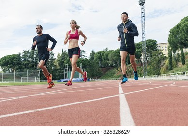Group of young  athletics people running on the track field