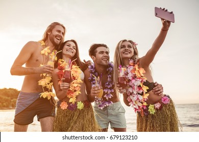 Group of young attractive friends are having fun on beach, smiling and making selfie. Party in Hawaiian style.