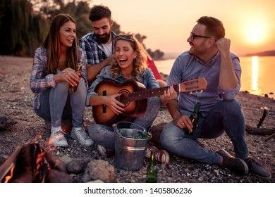 Group of young attractive friends are sitting next to river, playing  guitar and having fun.