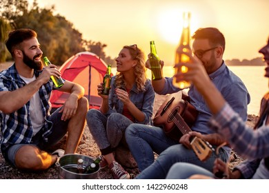 Group of young attractive friends are sitting next to river, playing the guitar and having fun.