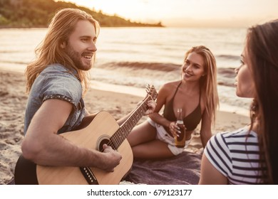 Group of young attractive friends are sitting on beach, playing the guitar and having fun.