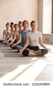 Group of young attractive people practicing yoga lesson doing Easy Seat exercise, Sukhasana pose, working out indoor full length, mixed race female students training at club or yoga studio. Copy spase