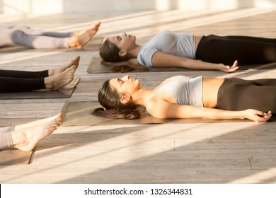 Group of young attractive people practicing yoga lesson doing Dead Body, Savasana exercise, Corpse pose, working out, indoor close up, mixed race female students training at club or yoga studio