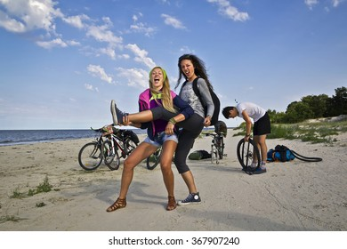 Group of young and attractive people standing on the sandy beach with bicycles fully equipped for a hike. Girls on foreground are having fun. Happy backpackers touring around the Baltic sea.