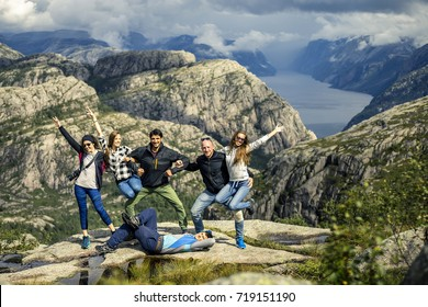 Group of young and attractive people standing on the mountain with raised up hands. Scenic fjord and sky on background. The way to Preikestolen, Norway.