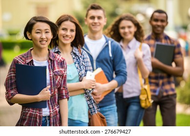 Group of young attractive smiling students dressed casual studying together in park.