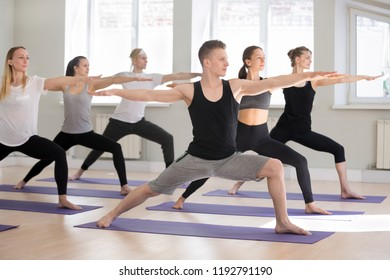 Group of young attractive sporty people practicing yoga lesson, doing Warrior Two exercise, Virabhadrasana II pose, working out indoor full length, students training in club studio. Well-being concept