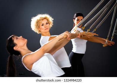 A group of young and attractive women training in the gym,stretching in tower reformer