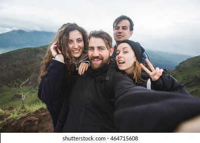 A group of young backpackers takes selfie photo portrait on the top of the mountain. Happy hipster multiracial friends make photo for their blog or social media.