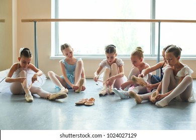 Group of young ballerinas preparing for performance. Six young ballet girls in ballet studio.