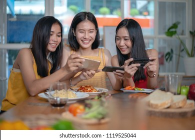 Group of young beautiful Asian woman eating food and taking photo by smartphone while talking about their general happy topic in restaurant.