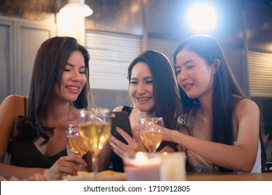 Group of young beautiful Asian woman eating food drinking alcohol and taking photo by smartphone while talking about their general happy topic in restaurant.