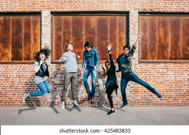 Group of young beautiful multiethnic man and woman friends having fun jumping outdoor in the city - happiness, friendship, teamwork concept