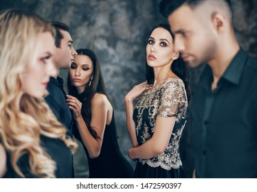 Group of young beautiful people posing in studio. Fashion photo concept