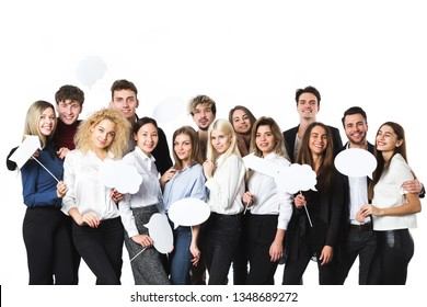 Group of young beautiful women and men in casual wear with clouds of thoughts tags in hands isolated on white background. Happy smiling people.