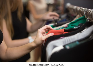 Group of young beautiful women shopping in fashion mall, choosing new clothes, looking through hangers with different casual colorful garments on hangers, close up of hands/ Shopping concept