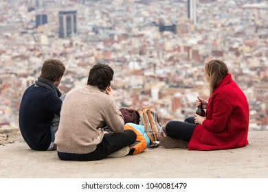 Group of young best friends drinking sitcoms with backpacks from the top of a peak watching the cityscape of Barcelona