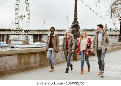 Group of Young Best Friends Making a Sightseeing Walking near London Eye close the Westminster Bridge. Friendship Concept with Multicultural People Enjoying and Having Fun on Vacation Holiday Trip.