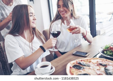 Group of young best friends with pizza and glass of drink celebrating in cafe interior.