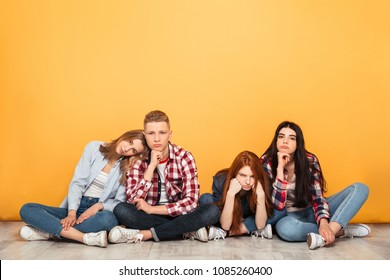 Group of young bored school friends sitting on a floor over yellow background