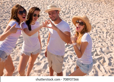 Group of young boys enjoying on a paradise beach with white t-shirts to wear vacation logos.