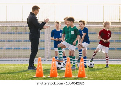Group of young boys on football training. Kids practicing soccer on grass field. Young man as a soccer coach explaing to players training rules. Children exercising with soccer balls