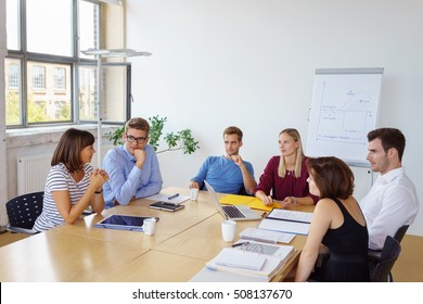 Group of young business entrepreneurs in a meeting grouped around a conference table having a discussion