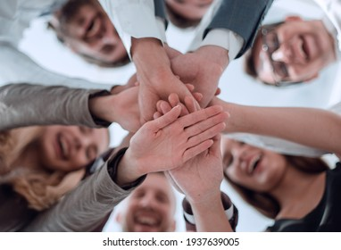 group of young business men clasping their hands together