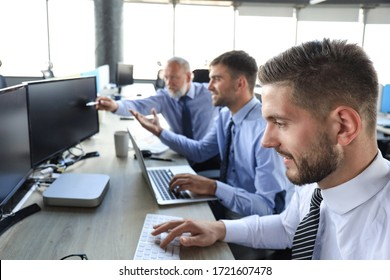 Group of young business men in formalwear working using computers while sitting in the office.