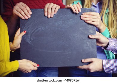 Group of young business partners standing with blank blackboard sign. Close up
