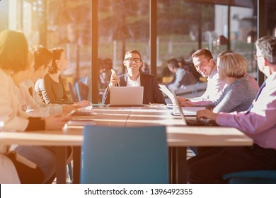 Gruppe von jungen Geschäftsleuten, die den Businessplan für ein Treffen im sonnigen, hellen Büro-Innern brainstorming und diskutieren