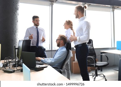 Group of young business people discussing something while working in the creative office