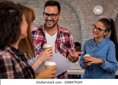 Group of young business people having conversation in office. Friends drinking coffee.