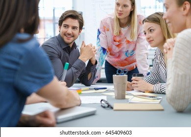 Group of young business people listening attentively to a colleague during a meeting in a low angle view across the table