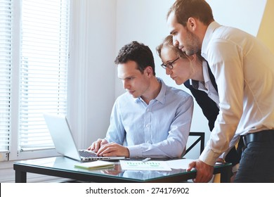 group of young business people looking at the screen of computer