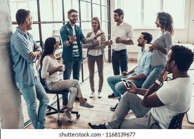 Gruppe der jungen Geschäftsleute in Break im Büro. Erfolgreiches Geschäftsteam spricht über Kaffeepause. Junge Lächelnde Kollegen über Break Drinking Coffee Chatting in Modern Office. Corporate Lifestyle