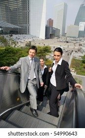 Group of young business people on an escalator