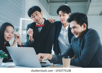 Group of young business people sit at their desks with smiling colleagues together in the office.  Meeting business people  planning concept, laptop meeting ideas. Concentrate on work. LGBT teamwork.