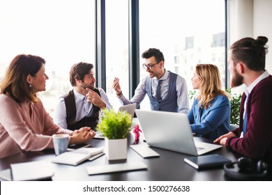 A group of young business people sitting in an office, having meeting.