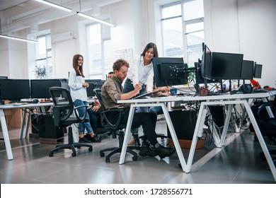 Gruppe junger Geschäftsleute, die mit Computern im modernen Büro arbeiten.
