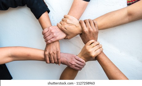 Group of young business people united, joining , combine hands together expressing positive, unity, volunteer , teamwork concepts.