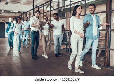 Group of Young Business People Walking Together. Successful Business Team Going thru Office. Young Smiling Colleagues Walking Together and Talking in Modern Office. Corporate Lifestyle