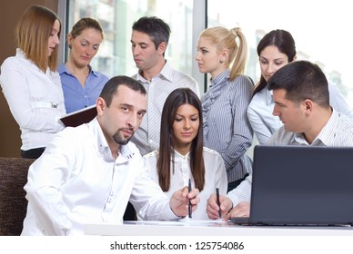 Group of young business people working in the office on laptop and discussing work