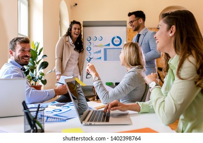 Group of young business people working together in office, two coworker conducting a business presentation using flip chart.