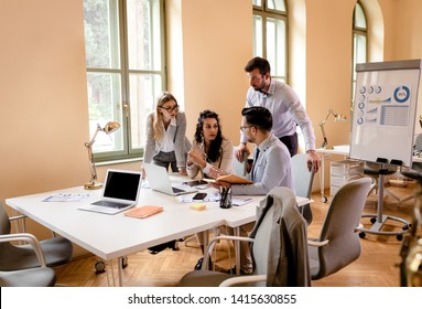 Group of young business people working together while sitting at the office desk.