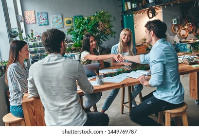 Group of young business people are working together in modern office. Creative people with laptop, tablet, smart phone, notebook. Successful hipster team in coworking. Freelancers.