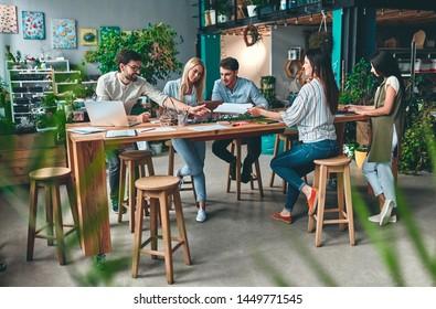 Eine Gruppe junger Geschäftsleute arbeitet im modernen Büro zusammen. Kreative Menschen mit Laptop, Tablet, Smartphone, Notebook. Erfolgreiches Hipster-Team bei der Mitarbeit. Freiberufler.