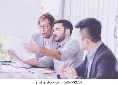 Group of young business people working, communicating while sitting at the office desk together with colleagues. Business people has stategic planning in office. Business concept.