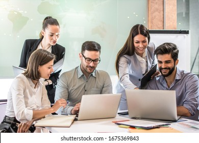Group of young business people working and communicating while sitting at the office desk together in the conference room